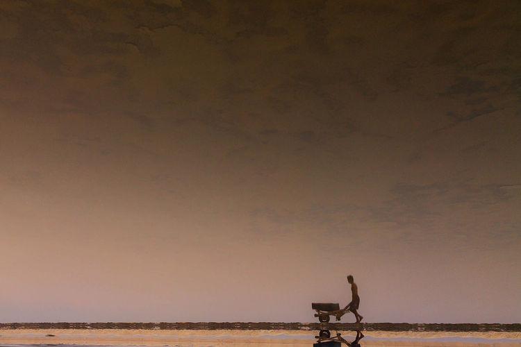 Manual worker pushing wheelbarrow against sky