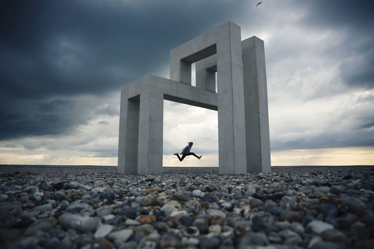 Full length of man jumping against built structure and sky