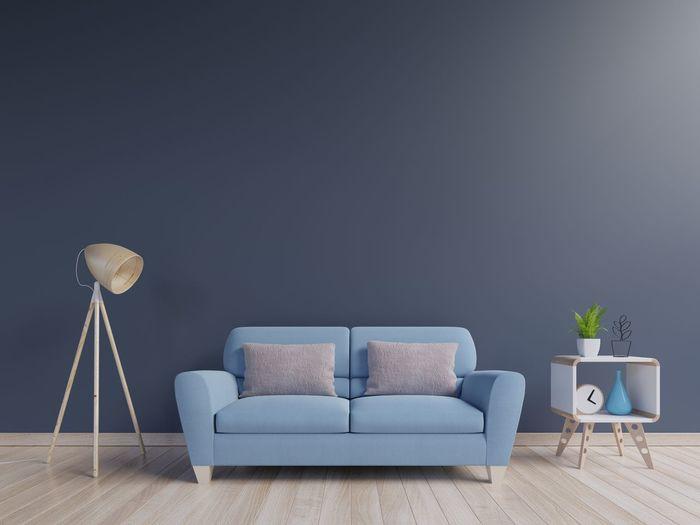 Empty Sofa By Lamp On Hardwood Floor Against Blue Wall