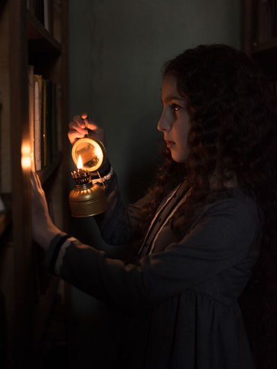 Side view of young woman holding burning candle