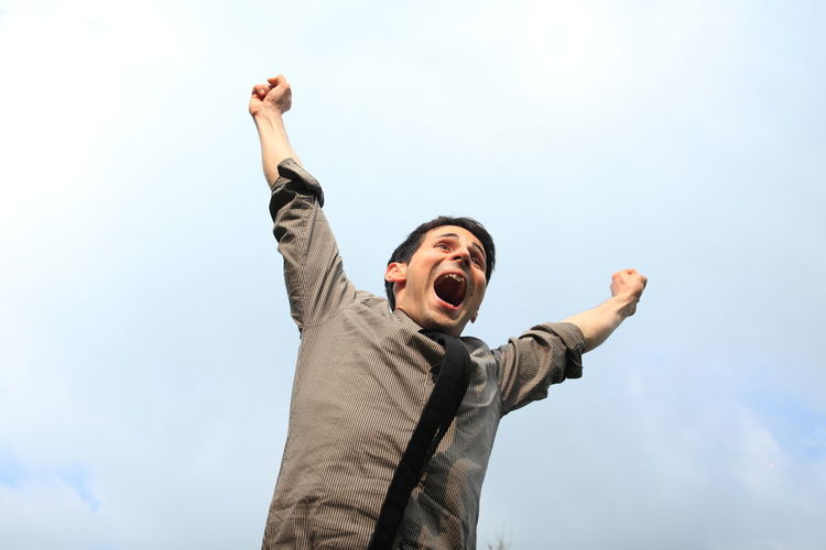 Low angle view of excited man with arms raised against sky
