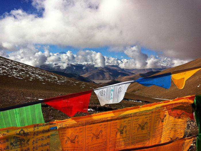 Low angle view of prayer flags against cloudy sky
