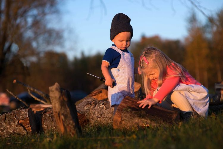 Siblings playing with log on grassy field in forest during sunset