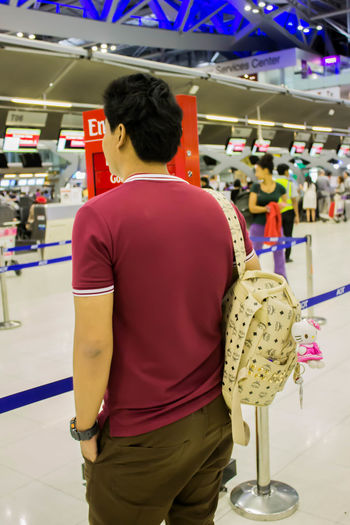 Adult Casual Clothing Focus On Foreground Hairstyle Illuminated Incidental People Indoors  Leisure Activity Lifestyles Men One Person Real People Rear View Retail  Shopping Short Hair Standing Store Three Quarter Length