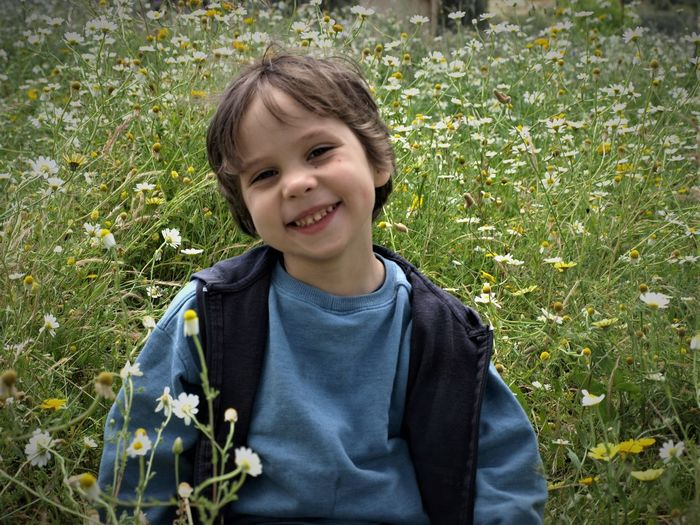 Portrait of smiling teenage boy standing amidst plants