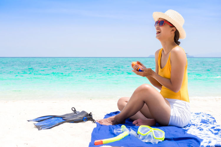 Happy young woman applying suntan lotion while sitting on beach against sky