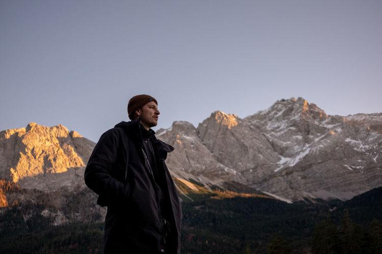 Man standing on rocks against mountain range