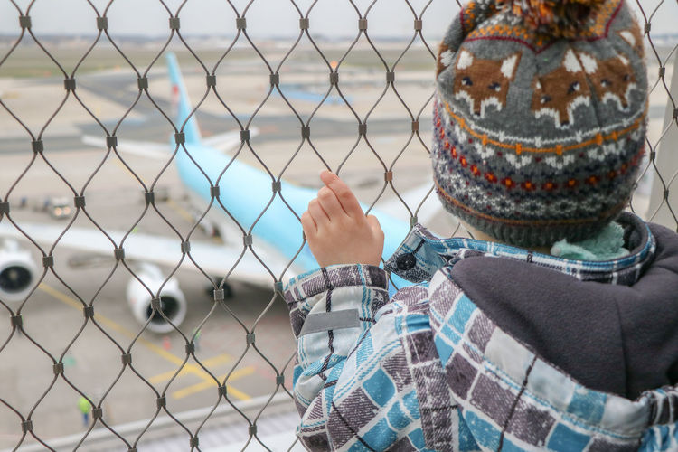 One Person Real People Focus On Foreground Day Rear View Fence Chainlink Fence Standing Child Childhood Security Holding Outdoors Warm Clothing Airplane Air Vehicle Airport Airport Runway Airport Terminal Terminal Transportation Travel Traveling Fascinating Boeing 747 Plane Security Metal Pattern Knit Hat EyeEm Best Shots Safety Barrier