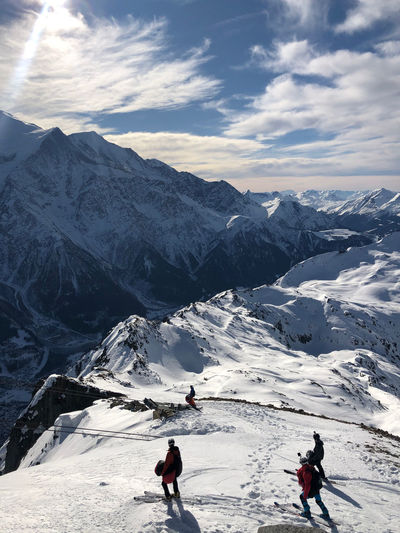 High angle view of people on snowcapped mountain against sky