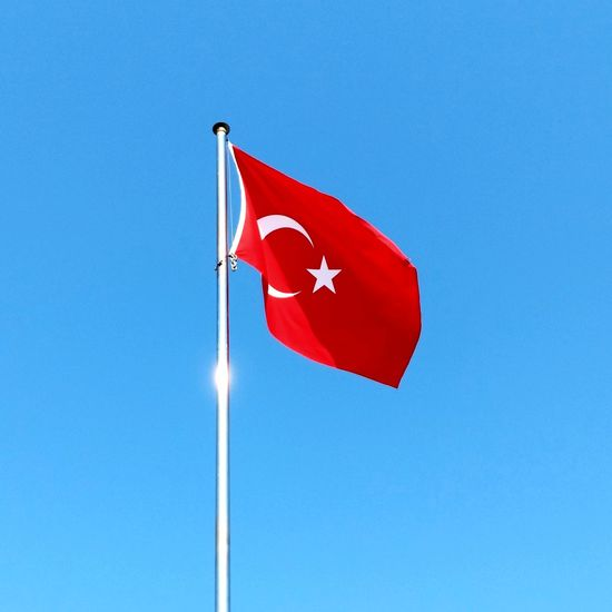 Low Angle View Of Turkish Flag Waving Against Clear Blue Sky