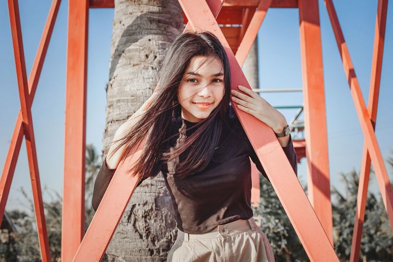 Portrait of beautiful smile women playing with red bridge and blue sky on background.
