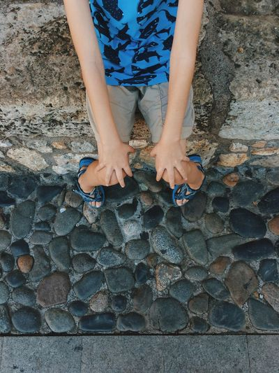 Low section of child standing on stone wall