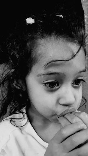 Close-up of innocent girl with hand in mouth