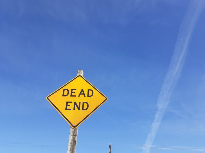 Road sign against blue sky