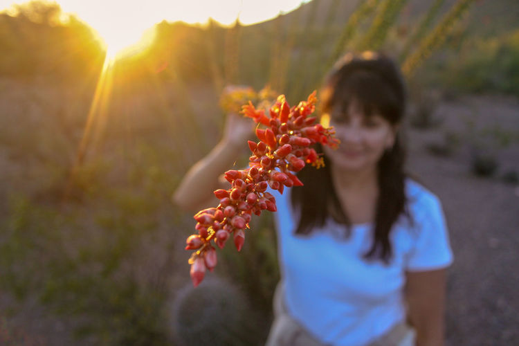 Woman holding flower on field during sunset