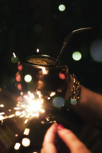 Tilt shift image of cropped woman holding burning sparkler with drink