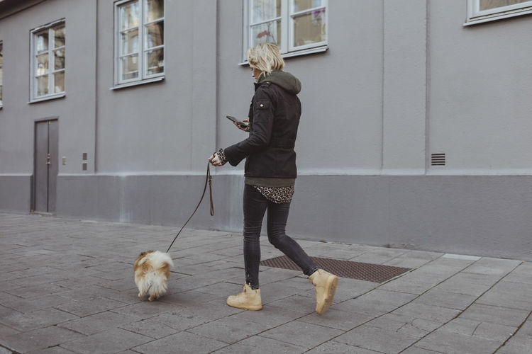 Full length of woman with dog on footpath