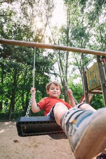 Portrait of smiling young woman sitting on swing at playground