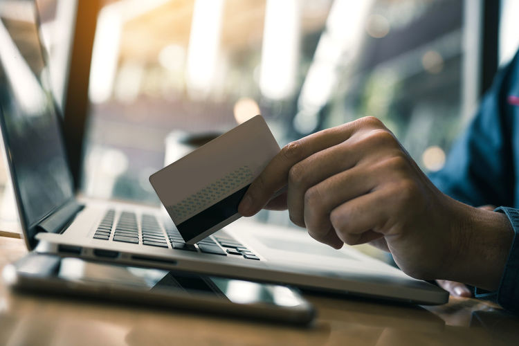 Cropped image of man holding credit card on laptop