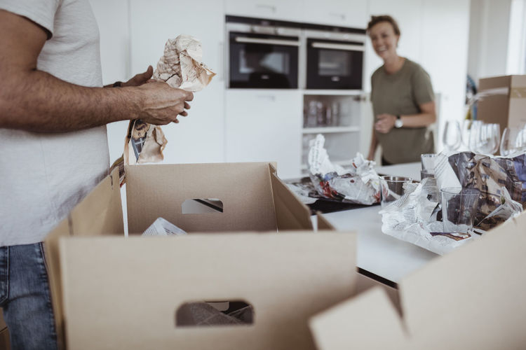 Midsection of woman holding paper in box at home