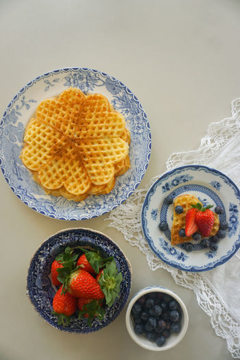 Norwegian waffles with fresh berries Norwegian Waffle Waffle Top View Directly Above High Angle View White Background Table Tablecloth Table Setting Blue Color Blue White Golden Cake Waffel Vafler Vaffel Berry Fruit Berry Berries Fruit Tart - Dessert Studio Shot Directly Above High Angle View Close-up Sweet Food Food And Drink Blueberry Berry Fruit