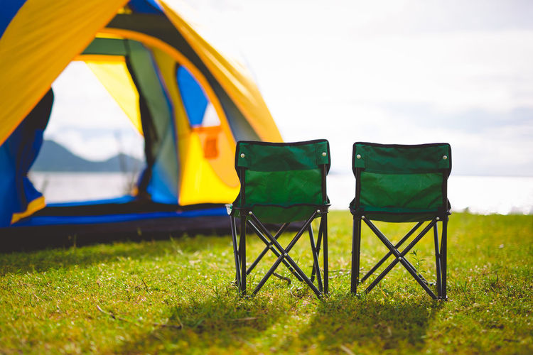 Empty chairs on grassy land at campsite