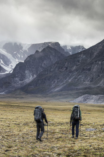 Rear view of men on snowcapped mountain against sky