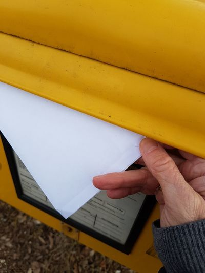 Cropped hand of person holding blank envelope by yellow mailbox