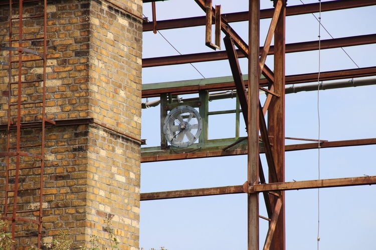 Abandoned building with a running fan propeller. Perspective Abandoned Buildings Architecture Brick Wall Built Structure Clear Day Electricity  Fan Propeller Low Angle View Nature No People No Walls Roof Beam Rusty Sky Steel Girders Window
