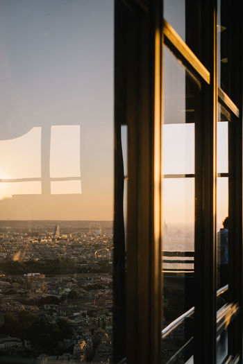 Buildings seen through window during sunset