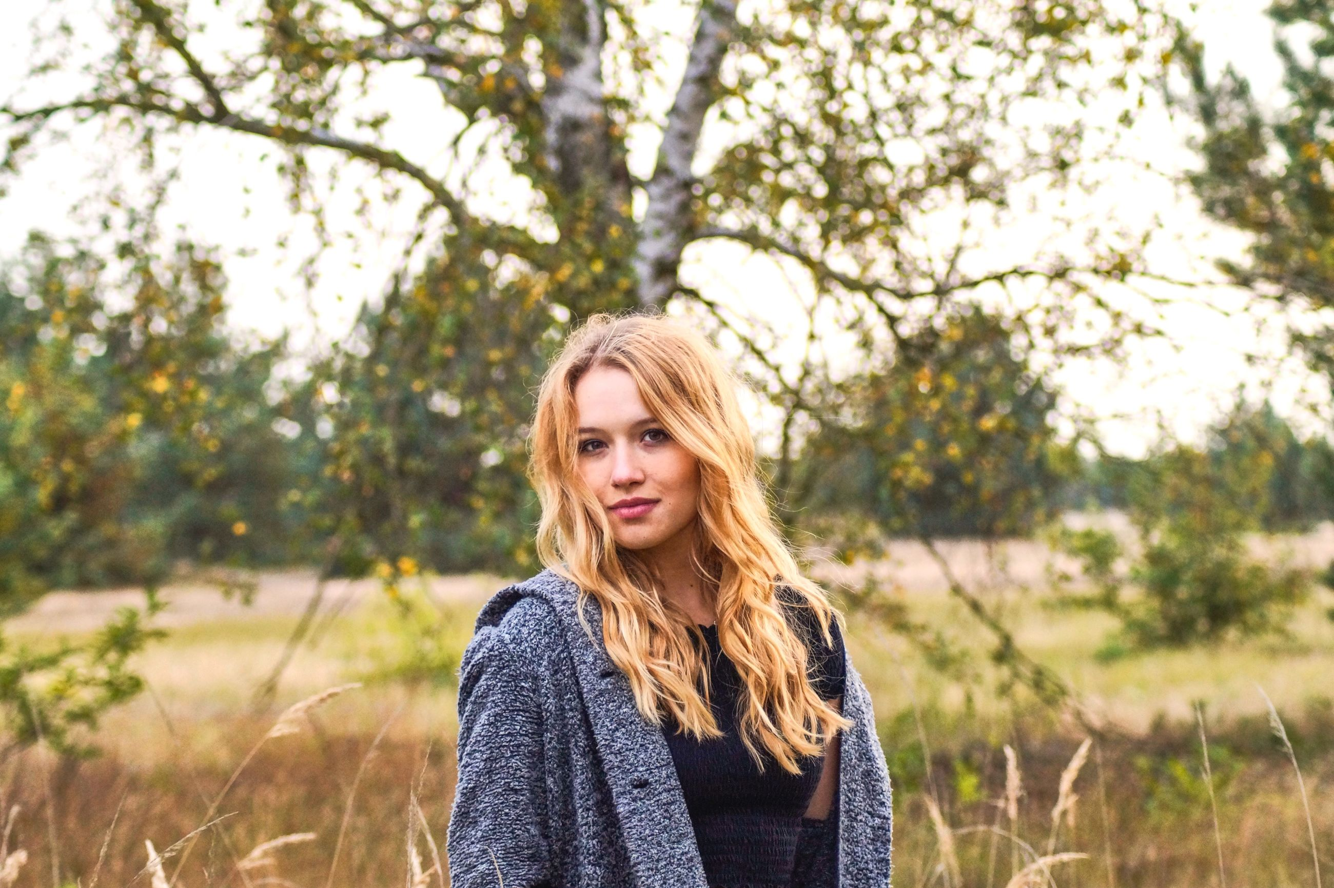 hair, portrait, long hair, young adult, tree, one person, hairstyle, blond hair, young women, plant, beautiful woman, looking at camera, real people, beauty, lifestyles, standing, women, day, focus on foreground, outdoors, teenager