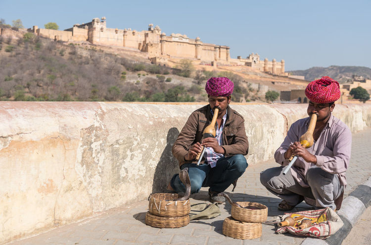 Snake charmers playing music for demonstration of the cobra dance Snake Charmer Musician Two People Snakes Are Beautiful Snake Charmers Sky Sitting Real People Playing Music Outdoors Men Lifestyles Day Communication Cobra Snake Amer Fort Jaipur Adults Only Adult Snake Jaipur Rajasthan Jaipur Artists Amer Castle, Castel