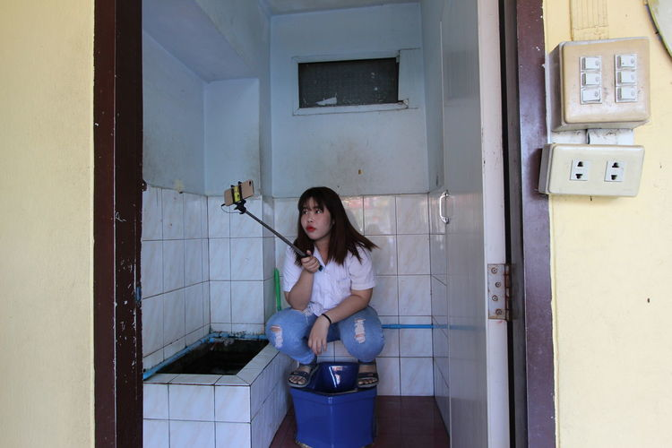 Young woman taking selfie on toilet bowl in bathroom at home