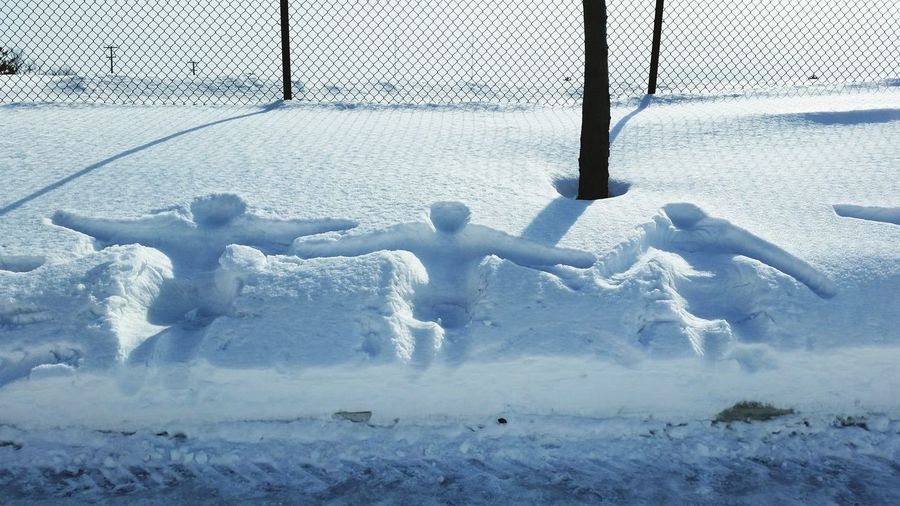 Human prints on snow covered land against fence