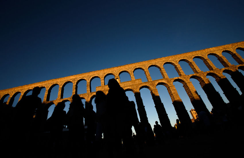 The Roman millennial aqueduct of Segovia, Spain, at sunset. Acueducto Aqueduct Historical Building Romantic SPAIN Ancient Civilization Arch Architecture Built Structure Clear Sky Heritage History Large Group Of People Lifestyles Low Angle View Men Night Outdoors People Real People Romanic Architecture Segovia Sky Sunset Women