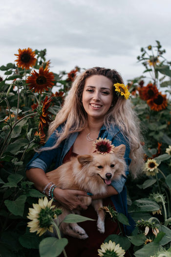 Portrait of woman with dog against plants