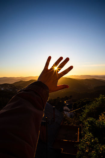 Cropped hand of person against mountains and sky during sunset