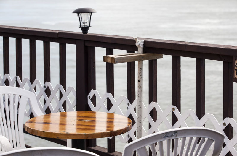 Empty Table And Chairs By Railing Against Sea At Ganghwado