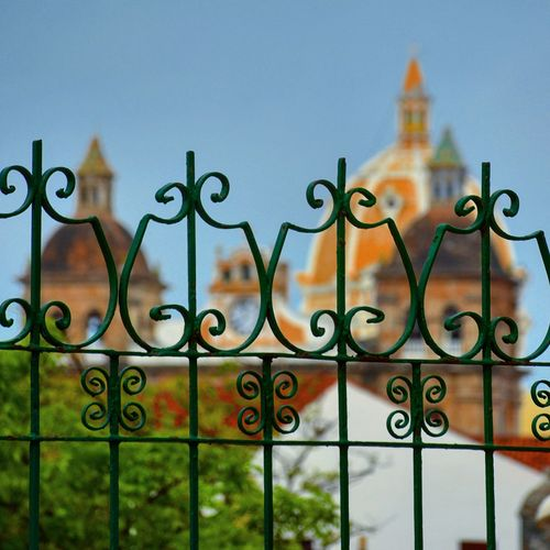Close-up of metal gate against cathedral in city