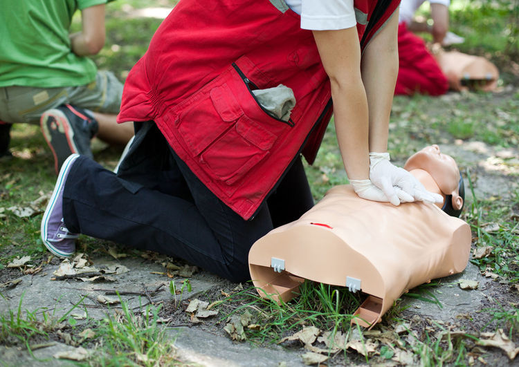 Low section of people practicing cpr on dummies at grassy field