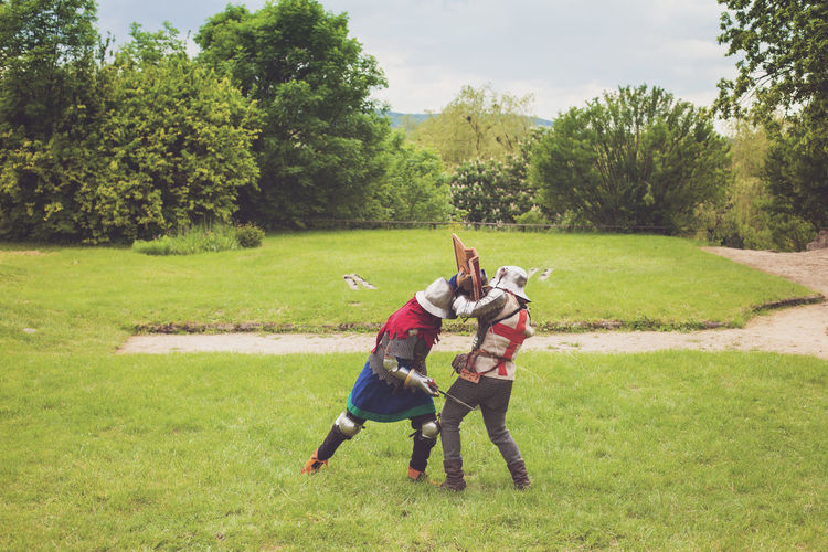 Two medieval knights in armor with swords and helmets are fighting on green grass Adult Ancient Battle Competition Day Fight Grass Helmet Knights Medieval Nature Outdoors People Protection Summer Sward Togetherness Tournament Tree