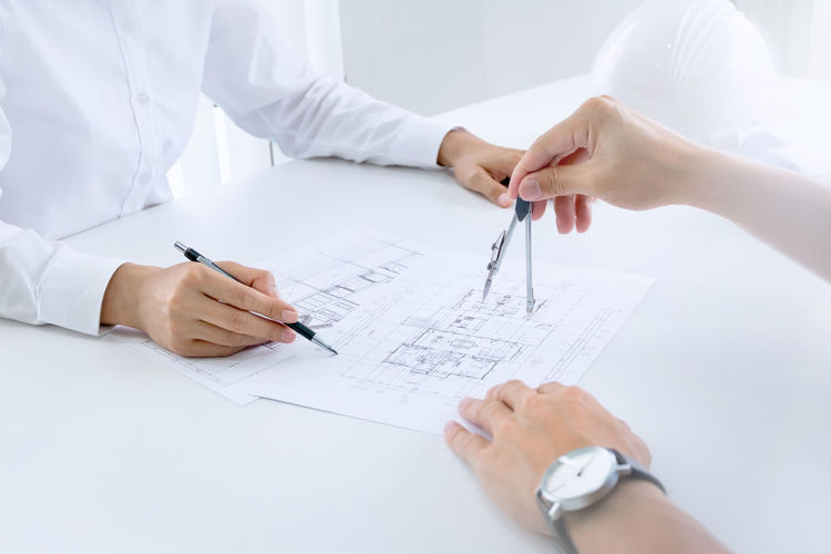 Engineers working on blueprint at office