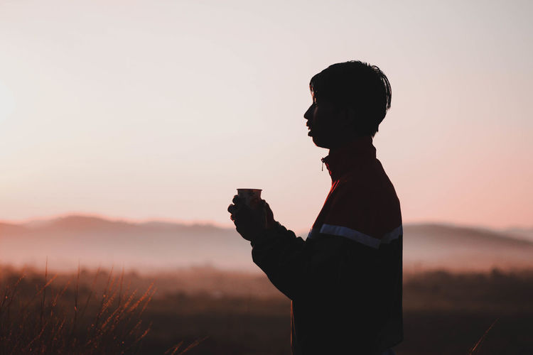 Side view of silhouette man having drink while standing against clear sky during sunset