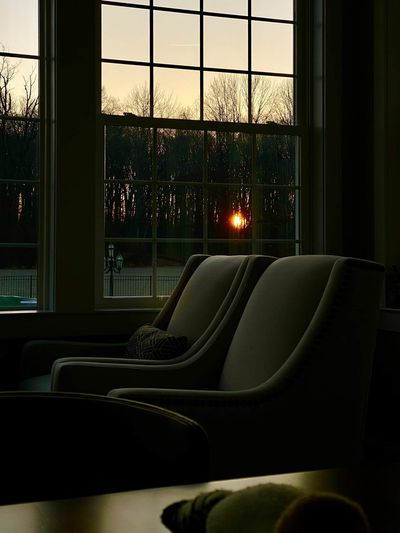 Empty chairs and tables against sky seen through window