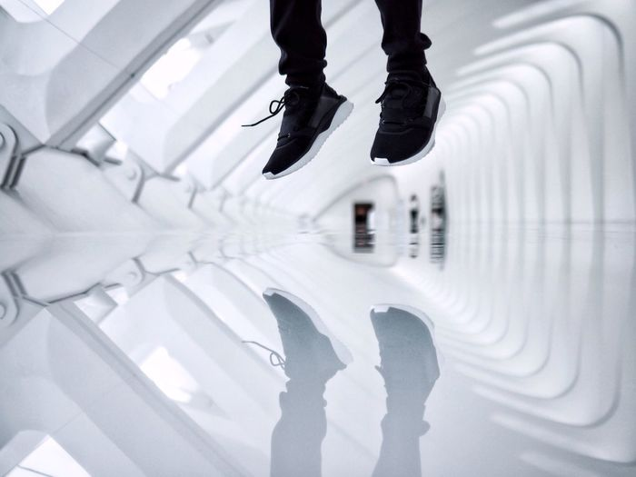 Low Section Of Person Jumping Reflected On Floor