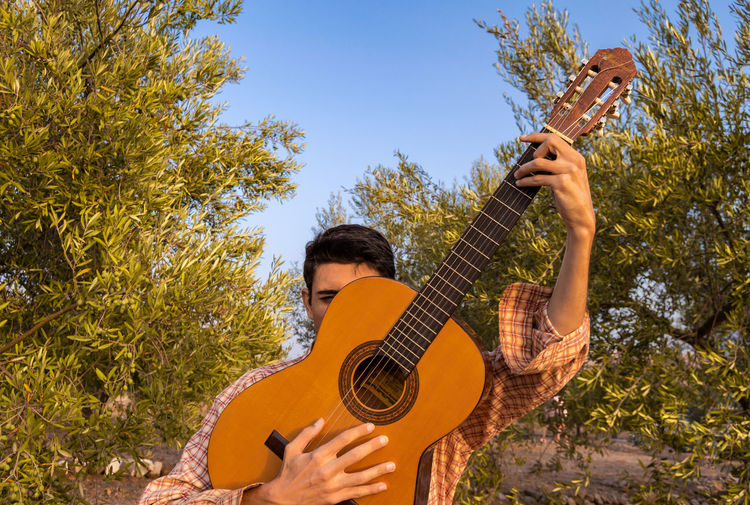 Young man holding guitar against trees