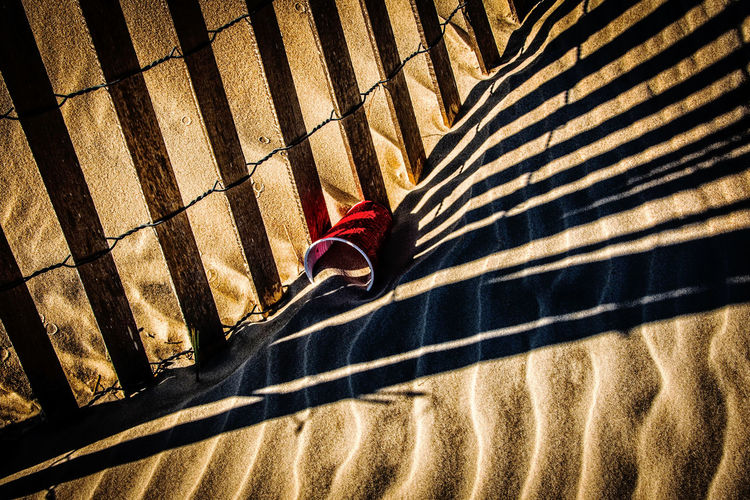 Shadow Of Fence On Sand At Beach