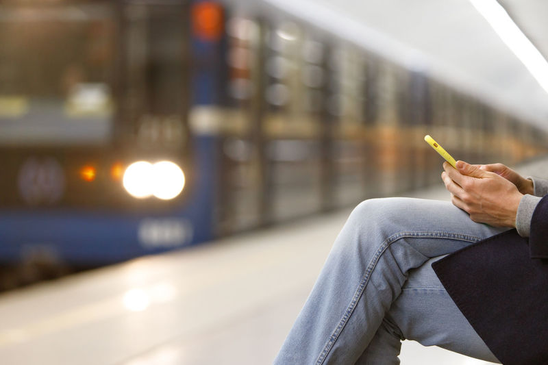 Midsection of man using phone at railroad station