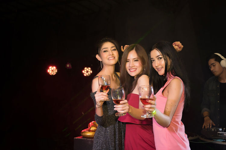 Portrait Of Happy Friends With Drinks Dancing In Nightclub