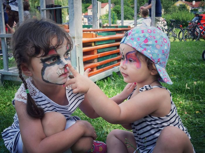 Cute sisters with face paints sitting on grass